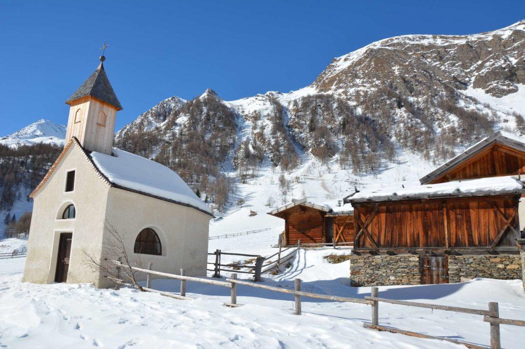 Der Winter auf der Fanealm ist wunderbar. Die Hütten sind weiß angeschneit, auf den Dächern liegt der Schnee.